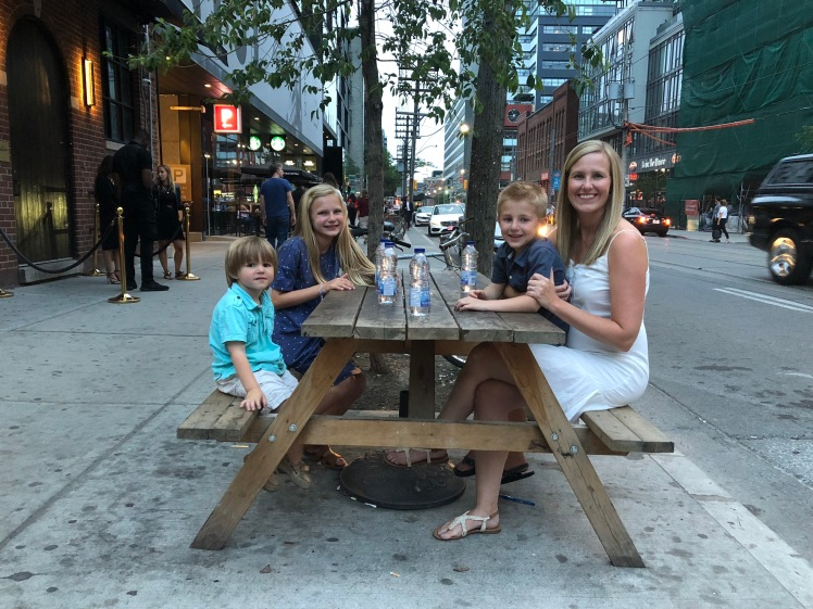 Michael's wife and three kids sitting at a picnic table near a busy street in downtown Toronto.