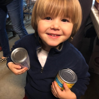 Our youngest son carrying cans in the church food pantry.