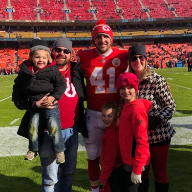 Michael and family with Kansas City Chiefs long snapper, James Winchester. Sidelines at Arrowhead Stadium in Kansas City.