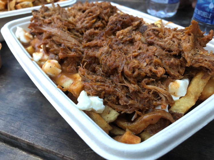 golden french fries topped with brown gravy and white cheese curds, which is all topped with juicy, barbecue pulled pork