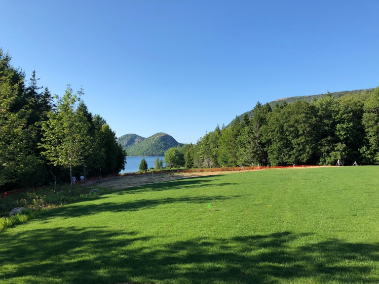 green lawn surrounded by tall, green trees, small opening at the back shows a view of the lake with twin hills covered in trees behind the lake. clear, blue sky, not a cloud in sight.